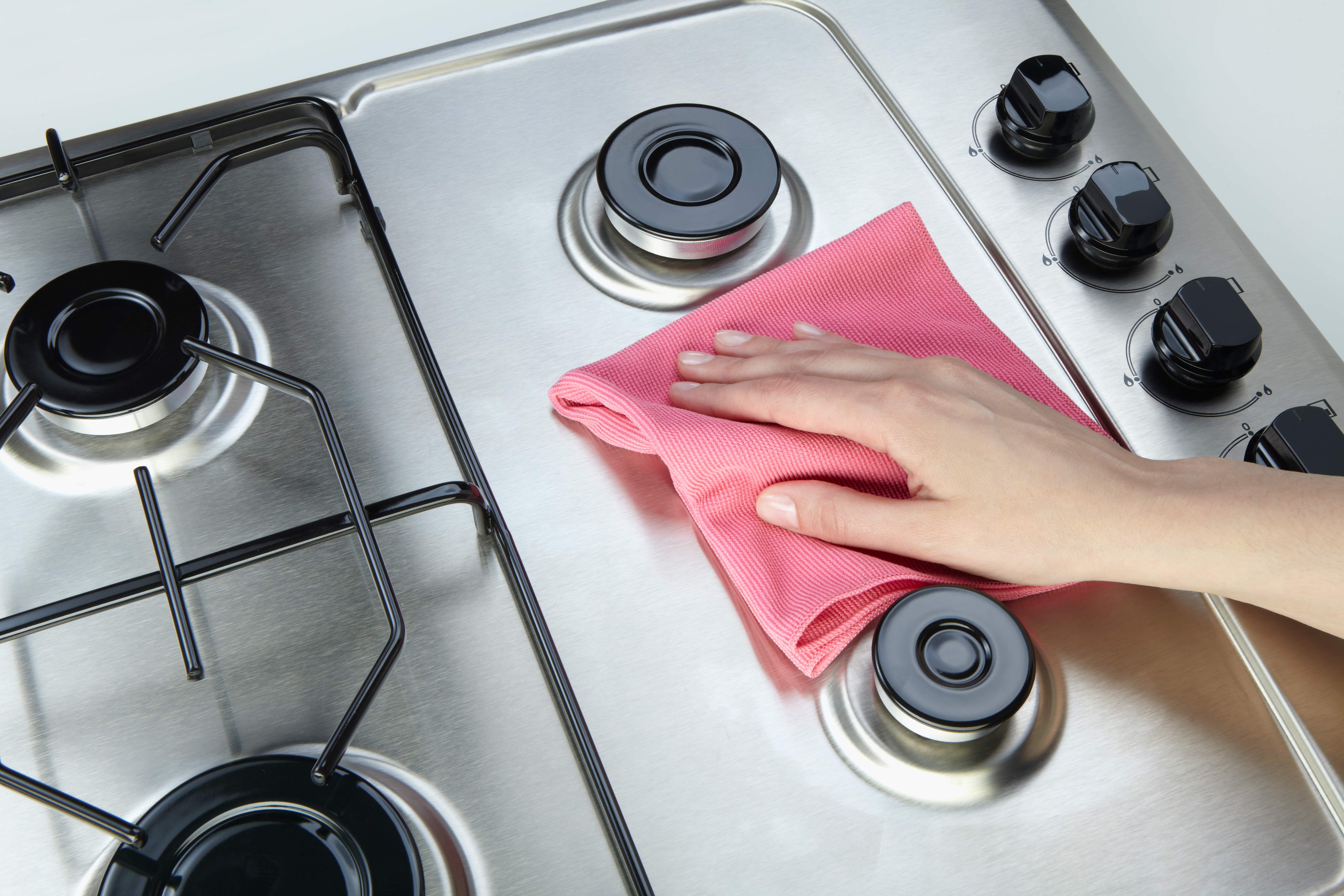 Person cleaning a stove
